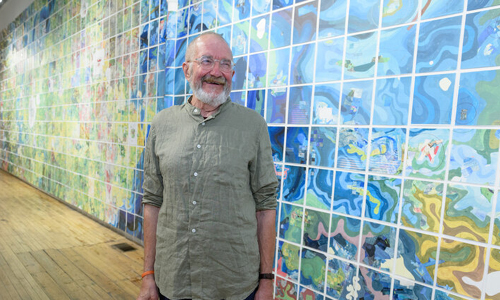Artist Jerry Gretzinger standing in front of his work.