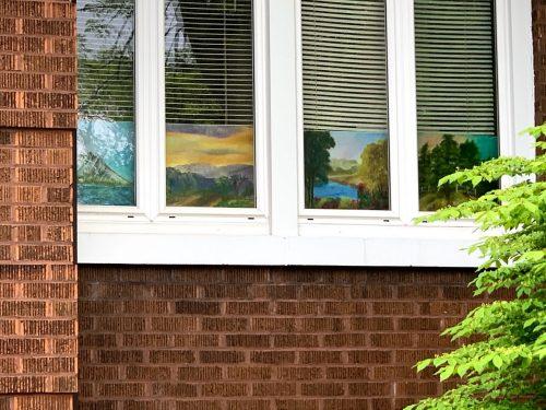 Landscape artworks displayed in a window