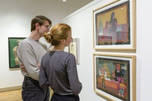 Two people looking at Eddie Arning paintings