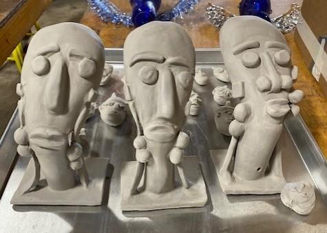 Three ceramic sculptures of faces