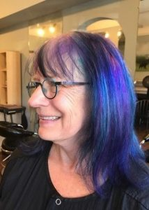 A woman with blue and purple hair in profile