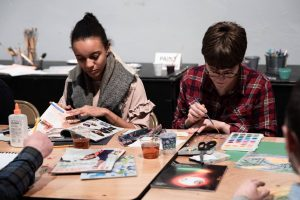 Two young adults creating art at a wooden table