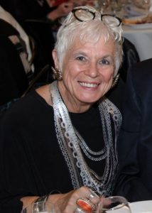 A woman with short white hair wears a black top with a long silver, silk scarf