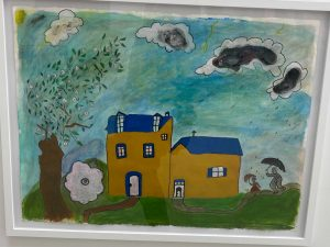 Yellow house with green grass and a blue sky with clouds by Rosena Finister