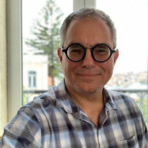 Ralph Concepcion in a plaid shirt and dark circular glasses