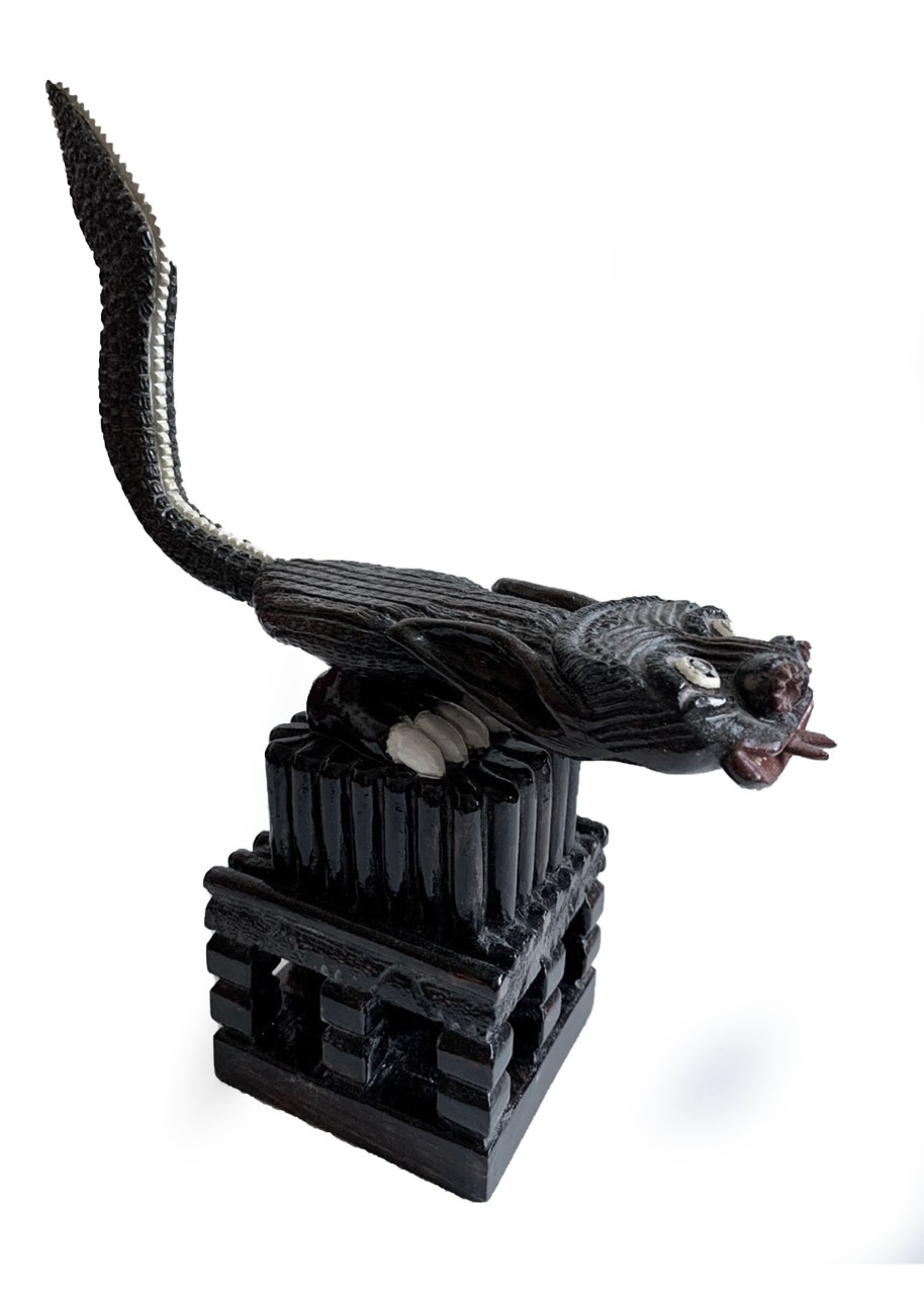 Black animal-like figure carved from wood atop a wooden box stand