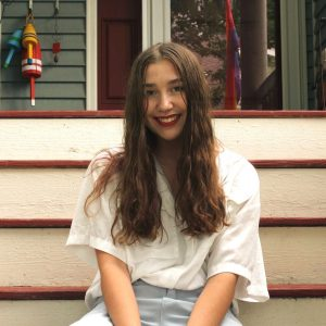 Skylar wears a white shirt and blue pants with her brown hair down, she sits on a set of white stairs
