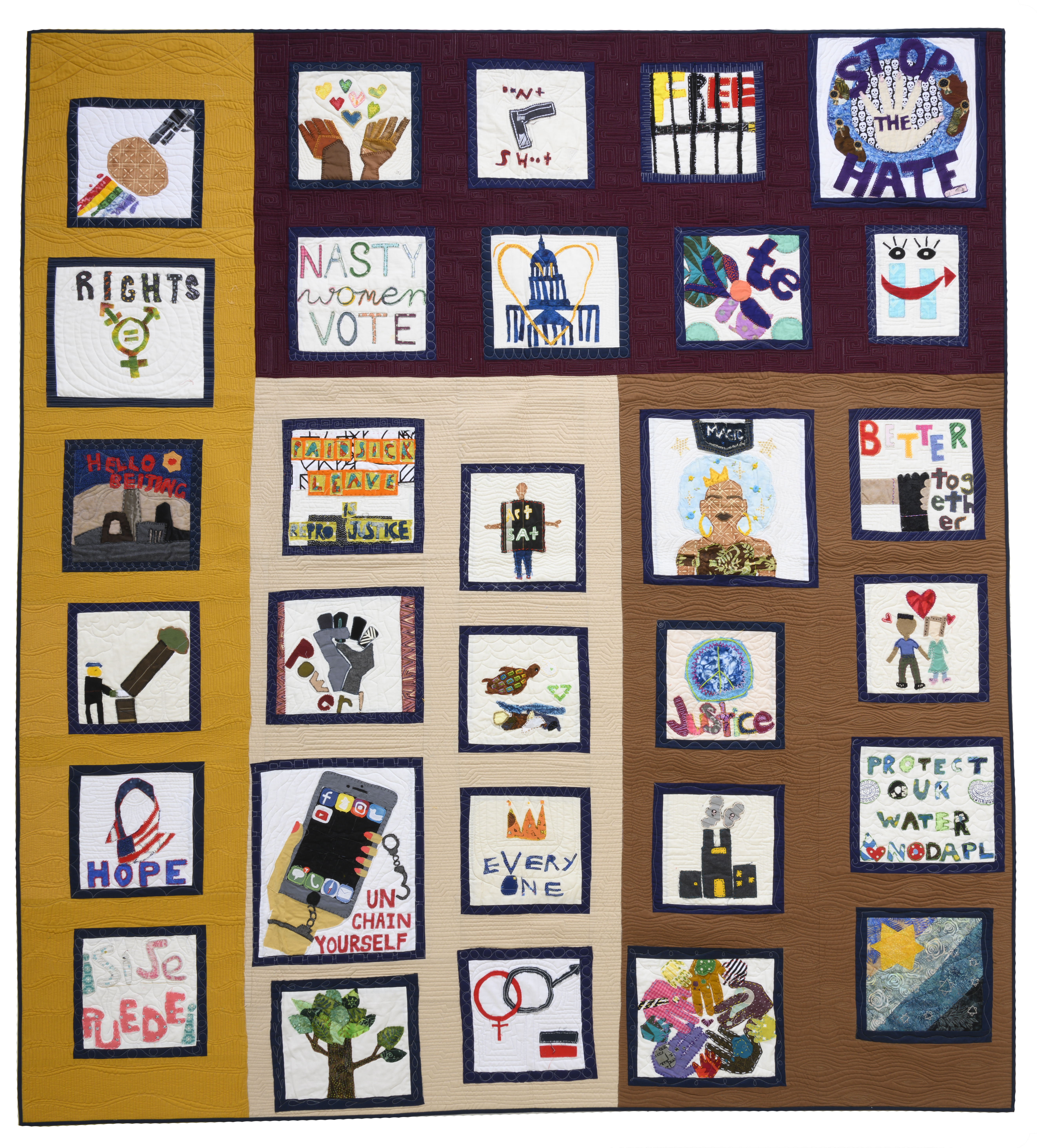 Photograph of a quilt with multicolored materials and blocks depicting social justice issues