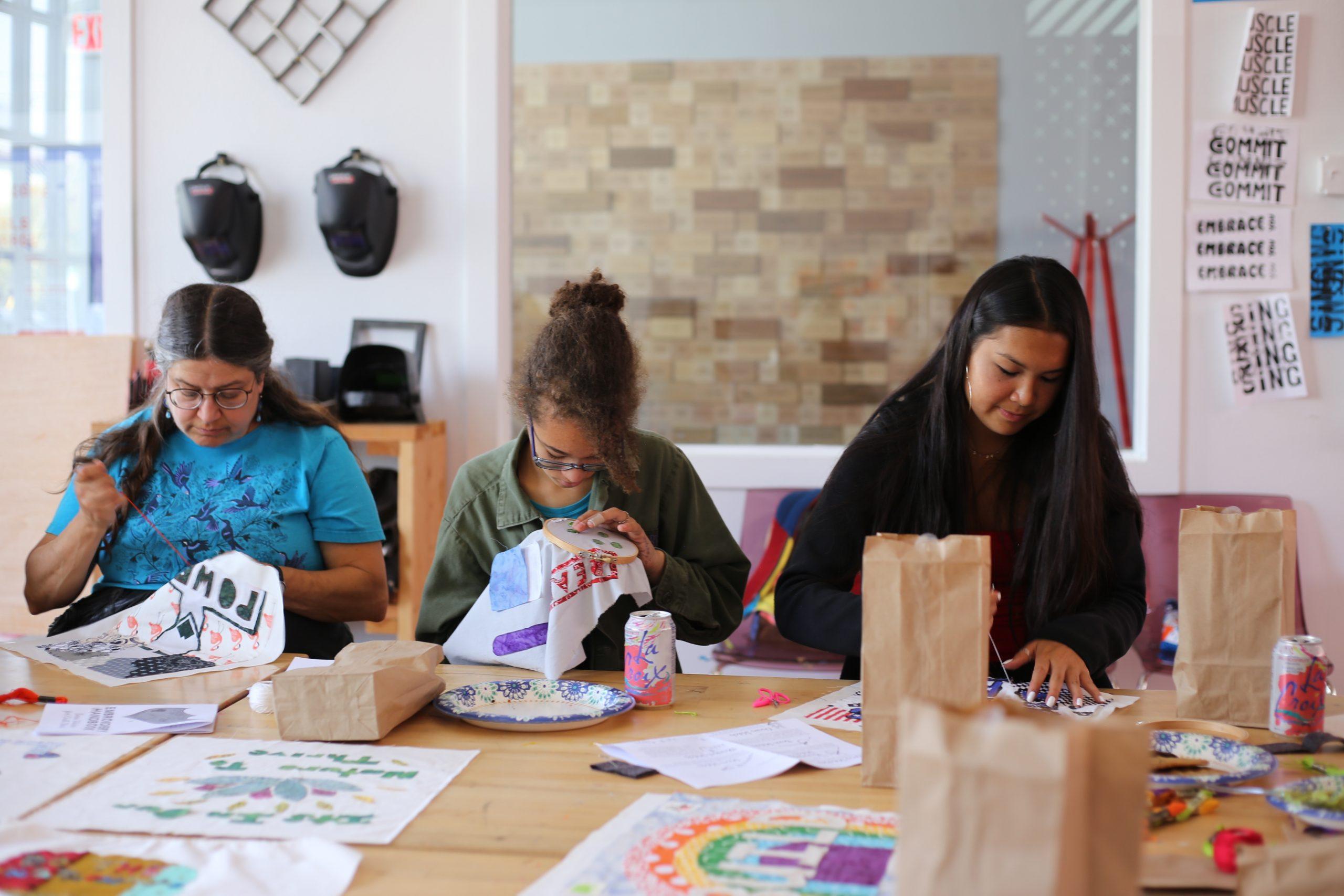 Photograph of three women sewing quilt blocks