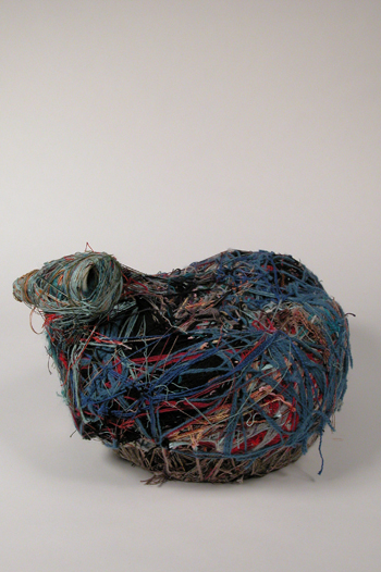 Photograph of a round sculpture comprised of found objects wrapped in yarn and string