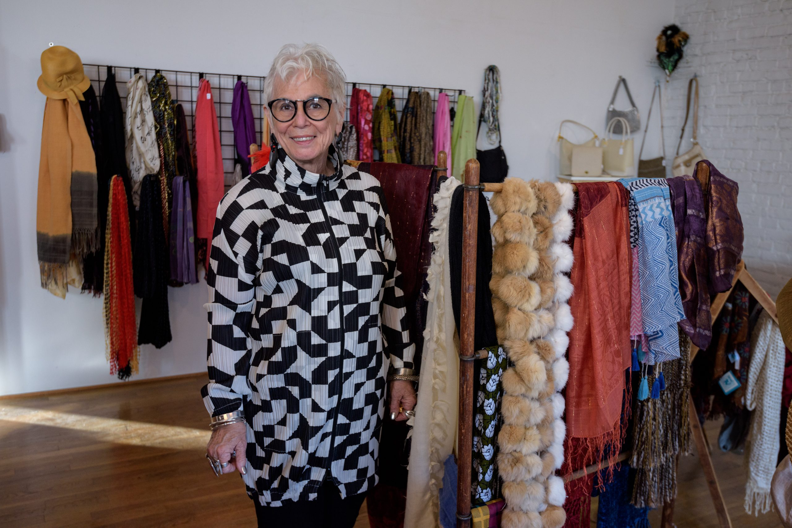 Photograph of a woman wearing a black and white patterned blouse, standing next to racks of clothing