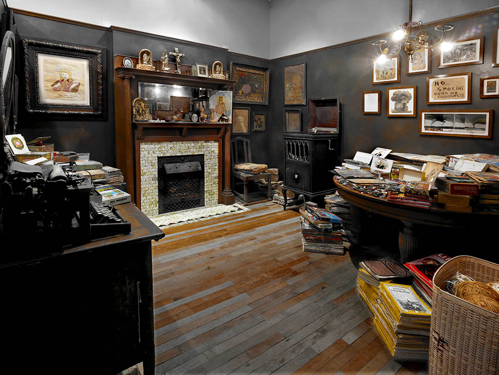 Installation photograph of the Henry Darger Room, its fireplace and table with paint materials