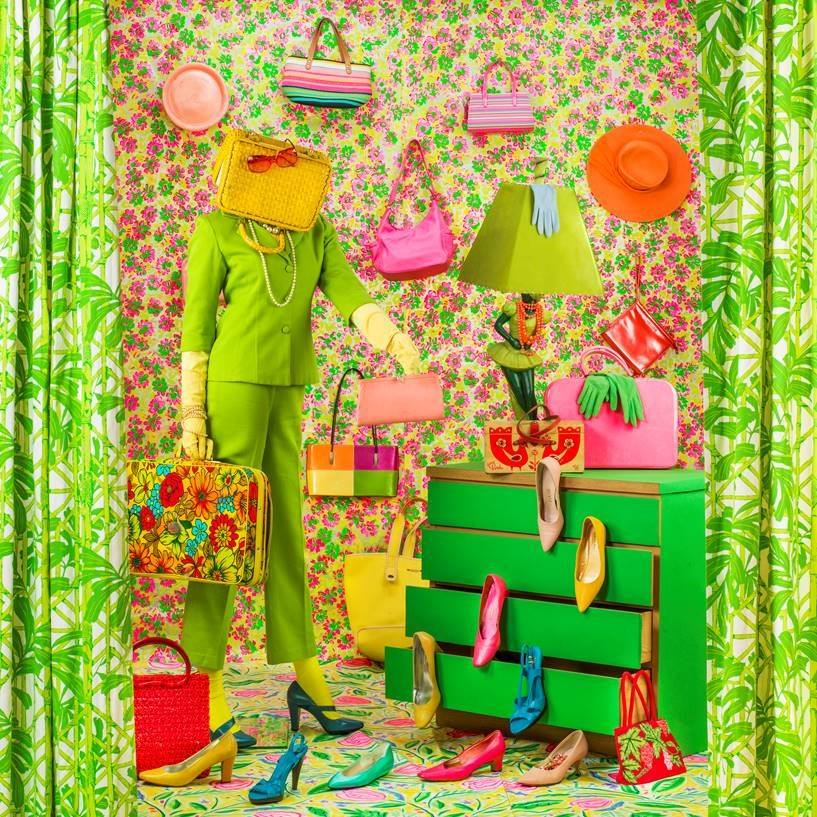 Pink, orange, yellow and green accessories and clothing items staged on a dresser and suitcase in front of a floral backdrop